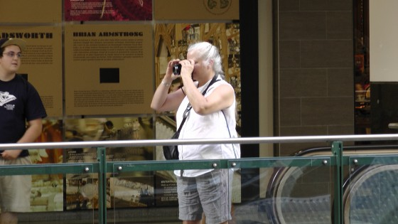 "Superfluous photo of an older woman taking a picture of ""Fragile"" by Roadsworth and Brian Armstrong at the Eaton Centre."