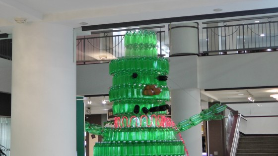 The head of a giant green snowman made out of recycled soda bottles.