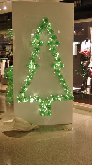 The outline of a Christmas tree made out of recycled soda bottles.